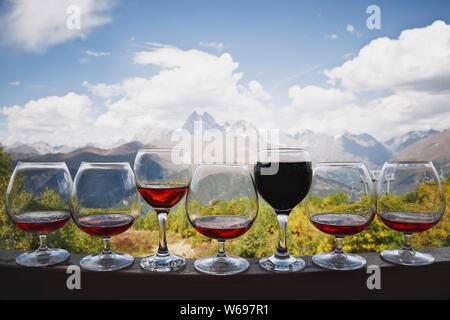 Fünf Gläser cognac und zwei Glas Rotwein und Rose Wein stehen vor dem Hintergrund einer wunderschönen Berglandschaft und die Seilbahn. Es gibt weiß - Stockfoto