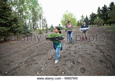 Multi-Generation Frauen, die Topfpflanzen im Garten - Stockfoto