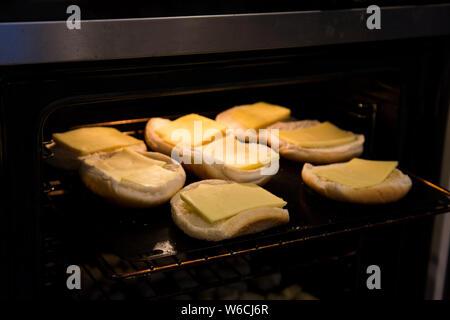Scheiben von milden Cheddar Käse unter dem Grill für zu Hause Familie Burger Nacht. Käse ist gelb, Brötchen sind weiß und Backofen ist dunkel - Stockfoto