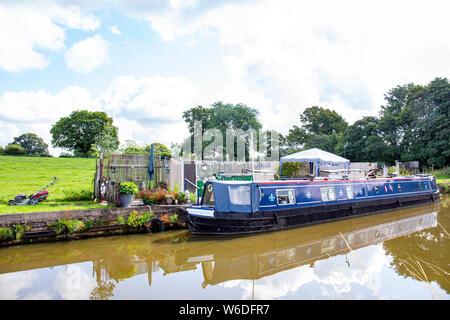Schmale Boot namens Shawthing Jesabel mit eigenem Garten festgemacht, und Messe, auf der Trent und Mersey Canal in Cheshire UK - Stockfoto