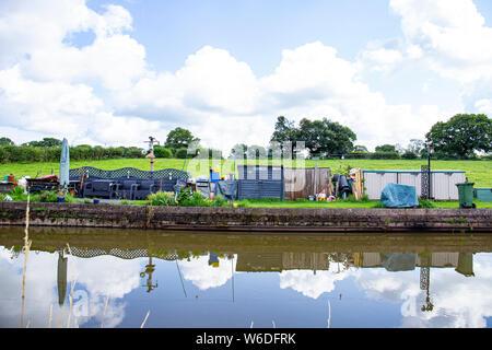 Reservierter Liegeplatz Platz für einen schmalen Boot genannt Moor Zeit mit eigenem Garten, und Messe, auf der Trent und Mersey Canal in Cheshire UK - Stockfoto