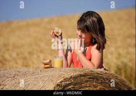 Kleines Mädchen essen ein Stück Brot mit Honig aus dem Berry, auf einem Strohballen im Sommer. Hinweis: Die Genehmigung für die redaktionelle Verwendung Achtung - Stockfoto