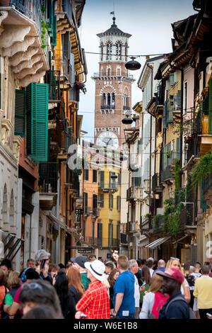 In Verona, Italien, Touristen Masse der modischen, bunten Fußgängerzone Via Giuseppe Mazzini. Im 12. Jahrhundert Turm der Lamberti steigt darüber hinaus. - Stockfoto
