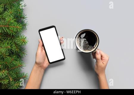 Weibliche Hände halten Schwarz Handy mit leeren weißen Bildschirm und Becher Kaffee. Mockup Bild mit kopieren. Ansicht von oben auf den lila ackground, La - Stockfoto