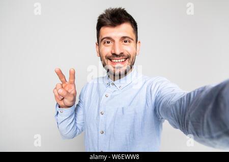 Close up Portrait von zufriedenen stattlichen achtlos unruhig mit strahlenden toothy Lächeln blogger auf grauem Hintergrund - Stockfoto