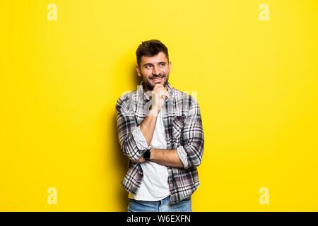 Close up Portrait von nachdenklicher Mann, der schaut weg sein Kinn berühren und wägt die Vor- und Nachteile des Angebotes isoliert auf hellen gelben backgrou - Stockfoto