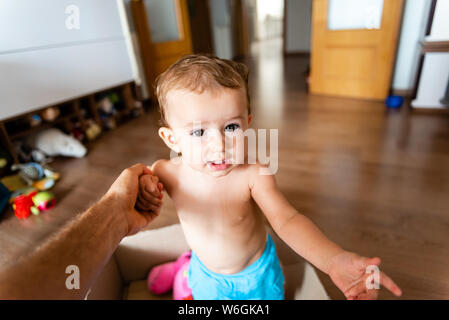 Der Vater hält die Hand seiner Tochter, sie aus einem Karton, in dem Sie spielt zu helfen. - Stockfoto