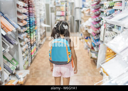 Kleines Mädchen im Geschäft mit Rucksack fertig für die Schule Material - Stockfoto