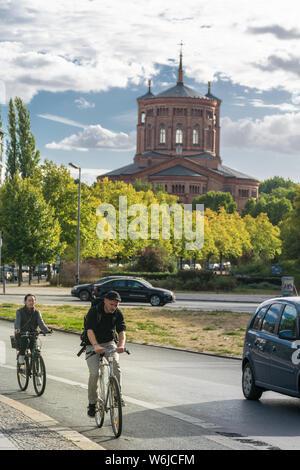 BERLIN, DEUTSCHLAND - 28. Juli 2018: Radfahrer reiten am ruhigen Straßen vor der evangelischen St. Thomas Kirche in Kreuzberg, Mariannenpl, die - Stockfoto