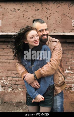 Bis zu schließen. Stilvolle Kerl umarmte seine geliebte Freundin. Das Konzept der Beziehung - Stockfoto
