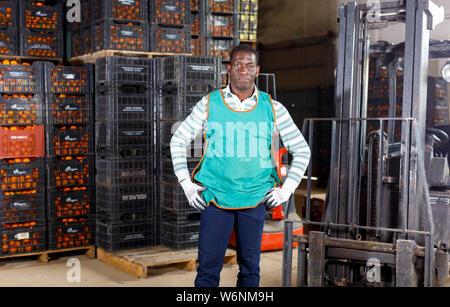 Portrait von afro Lagerarbeiter mit Lader im Lager von Mandarinen - Stockfoto