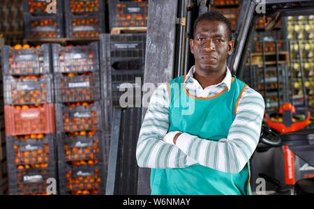 Portrait von afro Mann in der Nähe von Stapler im Lager posiert mit Mandarinen - Stockfoto