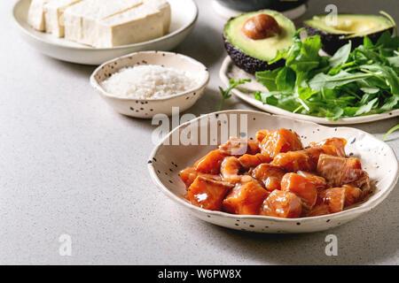 Zutaten zum Kochen poke Schüssel. Reis, Soja Sauce marinierter Lachs, Avocado, Tofu Käse und grünem Salat in Keramik Schalen auf Grau gefleckt. - Stockfoto