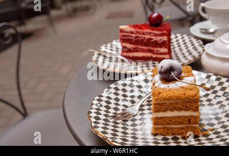 Und eine Kirsche auf der Oberseite - zwei Stücke aus verschiedenen Kuchen auf einem Tisch in einem Patio Cafe gesetzt - Stockfoto