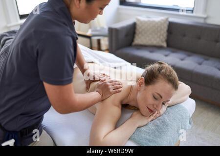 Chinesische Frau Massage therapist, eine Behandlung zu einer attraktiven Blondine Client auf Massage Tisch in einem hellen Medizinisches Büro - Stockfoto