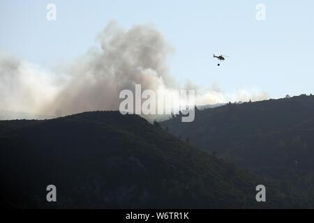 Sesimbra, Portugal. 2 Aug, 2019. Eine Brandbekämpfung Helikopter fliegt über den Rauch eines Feuers in Sesimbra, Portugal, August 2, 2019. Credit: Petro Fiuza/Xinhua Quelle: Xinhua/Alamy leben Nachrichten - Stockfoto