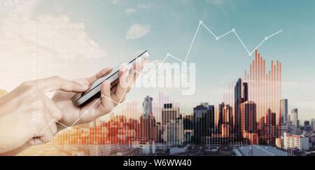 Hand, smart phone mit dem Anheben der Diagramme, die auf Stadt Hintergrund - Stockfoto