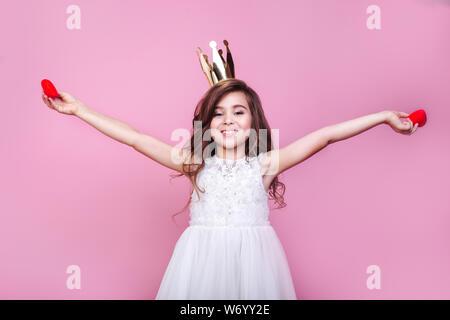 Kleines Mädchen im Kleid mit roten Herzen auf rosa Hintergrund - Stockfoto
