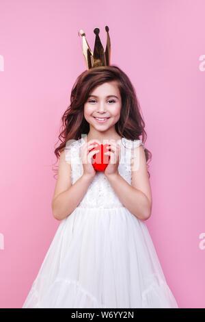 Kleine lockige Mädchen im Kleid holding Herz Anwendung lachend und an der Kamera auf rosa Hintergrund. - Stockfoto