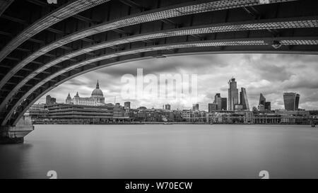 Der Blick auf die City von London aus unter der Blackfriars Bridge in London. Stockfoto