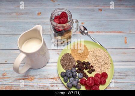 Glaskanne mit Getreide, Himbeeren und Heidelbeeren mit Milch für ein gesundes Frühstück gefüllt - Stockfoto