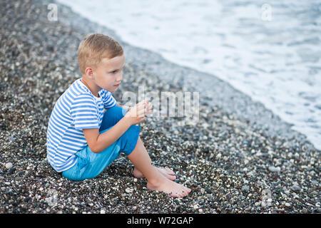 Junge in ein gestreiftes T-Shirt sitzen durch das Wasser am Strand in der Nähe. - Stockfoto