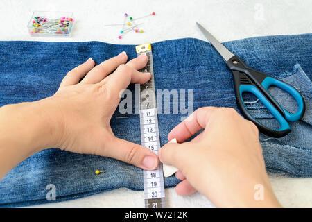 Frau Hände zeichnen eine Schnittlinie auf eine blaue Jeans. Jeans mit einem großen Loch auf einem hosebein in der Hälfte gefaltet und mit Pins maßgeschneiderte festgesteckt. Die Jeans zu kürzen. D - Stockfoto