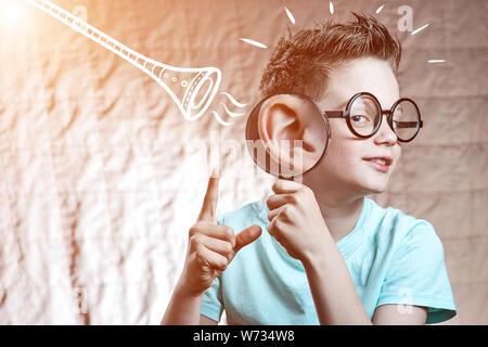 Ein Junge in einem hellen t-shirt Kontrollen Anhörung durch ein Rohr - Stockfoto