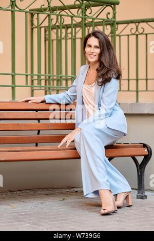 Stilvolle Frau in himmelblau Hosenanzug in Ruhe auf einer Bank in der Nähe des Amtes - Stockfoto