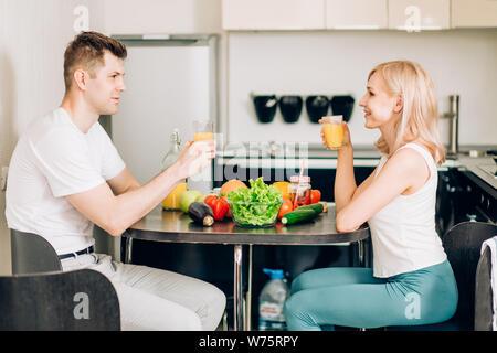 Schöne junge Paar spricht, an jedem anderen suchen und lächelnd während Sie frühstücken, trinken frisch gepressten Orangensaft, eine tolle Zeit zusammen - Stockfoto