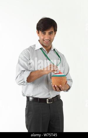 Verkaufsleiter für Münzeinwurf in ein Sparschwein - Stockfoto