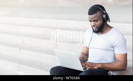 Konzentriert afrikanischen Kerl in Kopfhörer Eingabe auf seinem Laptop - Stockfoto