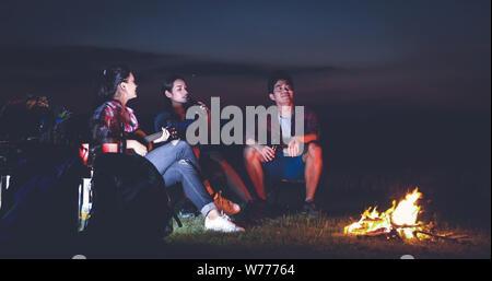 Eine Gruppe von asiatischen Freunden touristische trinken und Gitarre spielen zusammen mit Glück im Sommer beim Campingplatz in der Nähe von See bei Sonnenuntergang - Stockfoto