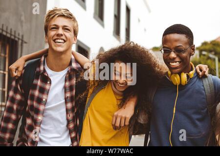 Nahaufnahme von drei College Freunde auf der Straße stehend mit Arme um einander. Fröhlichen Jungen und ein Mädchen mit college Taschen Spaß zu Fuß