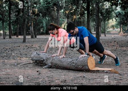 Paar tun Push-ups auf einem Baumstamm in einem Park - Stockfoto