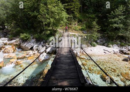 Frau Kreuzung eine hölzerne Hängebrücke über schöne türkisblaue Fluss Soca während Trekking auf dem Trail, Bovec Soca, Slowenien, Europa - Stockfoto