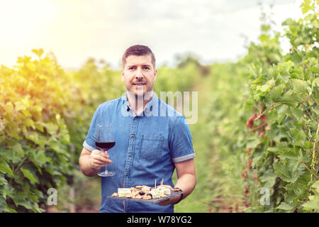 Gerne erfolgreiche Winzer im Weinberg holding Glas Rotwein und Board mit Käse, Nüssen und Trauben - lächelnde Menschen auf der Farm house Weingut Weinprobe - Stockfoto