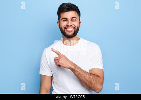 Jungen gutaussehenden charmanten Mann etwas mit Zeigefinger, Platz für Text, Werbung, kopieren. auf blauem Hintergrund isoliert. Richtung. Körper lang - Stockfoto