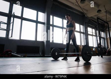 Auf den Erfolg konzentriert. Attraktive starke Muskulatur weibliche Bodybuilder tun heavy duty hockt Anheben barbell Am crossfit Fitnessraum - Stockfoto