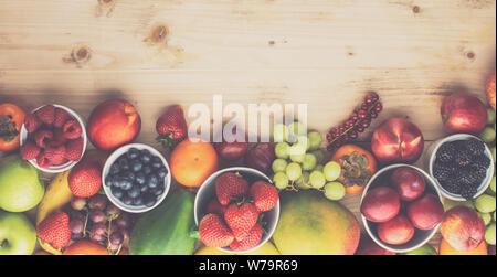 Fröhlich bunte Früchte Beeren, Erdbeeren, Orangen, Pflaumen Trauben mango Papaya rote Johannisbeeren Pfirsiche auf Holztisch, Ansicht von oben, straff, Banner, selecti - Stockfoto