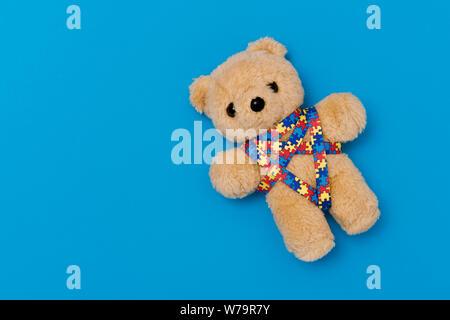 Welt Autismus Bewußtsein Tag, psychische Gesundheit Konzept mit Teddybär und Farbband puzzle Muster. Auf blauem Hintergrund - Stockfoto