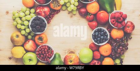 Rainbow Früchte Hintergrund Kreis Rahmen, Pflaumen Erdbeeren Himbeeren Orangen, Äpfel, Kiwis, Weintrauben, Heidelbeeren mango auf Holztisch, Ansicht von oben, Kopieren s - Stockfoto