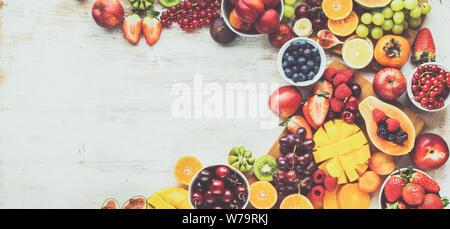 Gesunde rohe Früchte Hintergrund, Mango, Papaya, Orangen, Pflaumen Erdbeeren Himbeeren Äpfel, Kiwis, Weintrauben, Kirschen, Blaubeeren auf weißem Tabelle, kopieren - Stockfoto