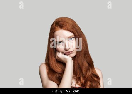 Gefühl umgekippt. frustrierte Mädchen mit roten Haaren die traurige Gesicht, während gegen grauen Hintergrund stehen. Menschliche Gefühle. Negativität - Stockfoto