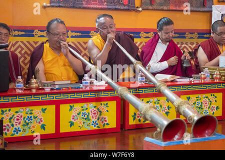 Nepalesische buddhistische Mönche spielen Die dungchen Traditionellen langen Horn bei einem Gebetstreffen. An der Sherpa Kyidug Tempel in NYC. - Stockfoto