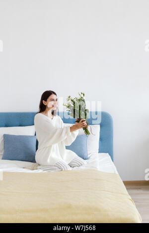 Ein Mädchen in einem weißen Pullover sitzt auf einem Bett mit einem Blumenstrauß aus den weißen Rosen in ihrer Hand - Stockfoto