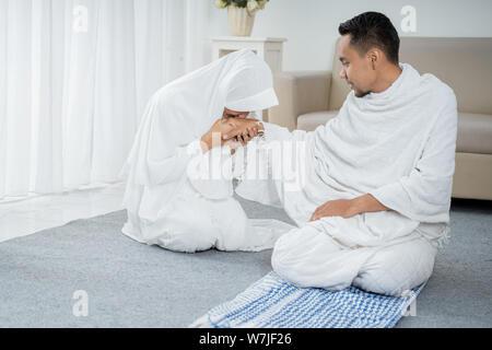 Nach sholat Frau küssen Mann Hand tragen weiße traditionelle Kleidung - Stockfoto