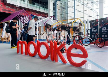 Menschen besuchen den Stand der Chinesischen bike-sharing service Mobike während einer Ausstellung in Dalian im Nordosten der chinesischen Provinz Liaoning, 25. Juni 2017. - Stockfoto