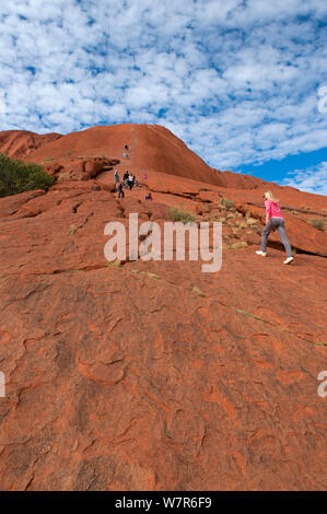 Touristen zu Fuß bis Uluru/Ayers Rock, Uluru Kata Tjuta National Park, Northern Territory, Australien - Stockfoto