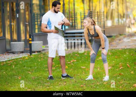 Männliche personal trainer zeigen Ergebnisse zu Ihren weiblichen Kunden - Stockfoto